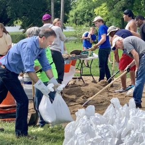 County Executive Sam Page sandbags Tuesday in Bellefontaine Neighbors, with the help of volunteers.