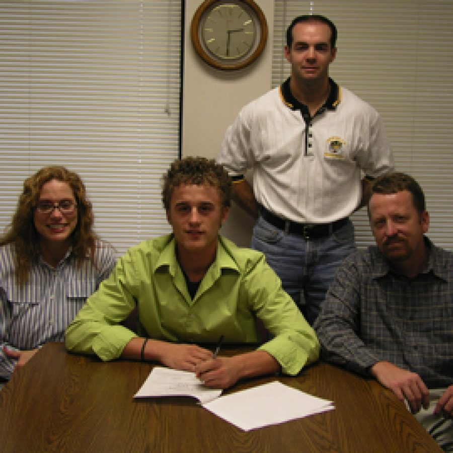 Oakville Senior High School baseball player Andy Marks signs his letter of intent with the University of Kansas. Shown with Marks are his parents, Nanette and Kevin Marks, and baseball coach Rich Sturm, standing.