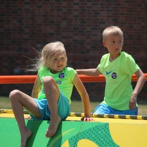Siblings Anders and Vaeya Rhodes climb on The Magic House playground in summer 2018. They both wore neon green shirts to the event, so that they
