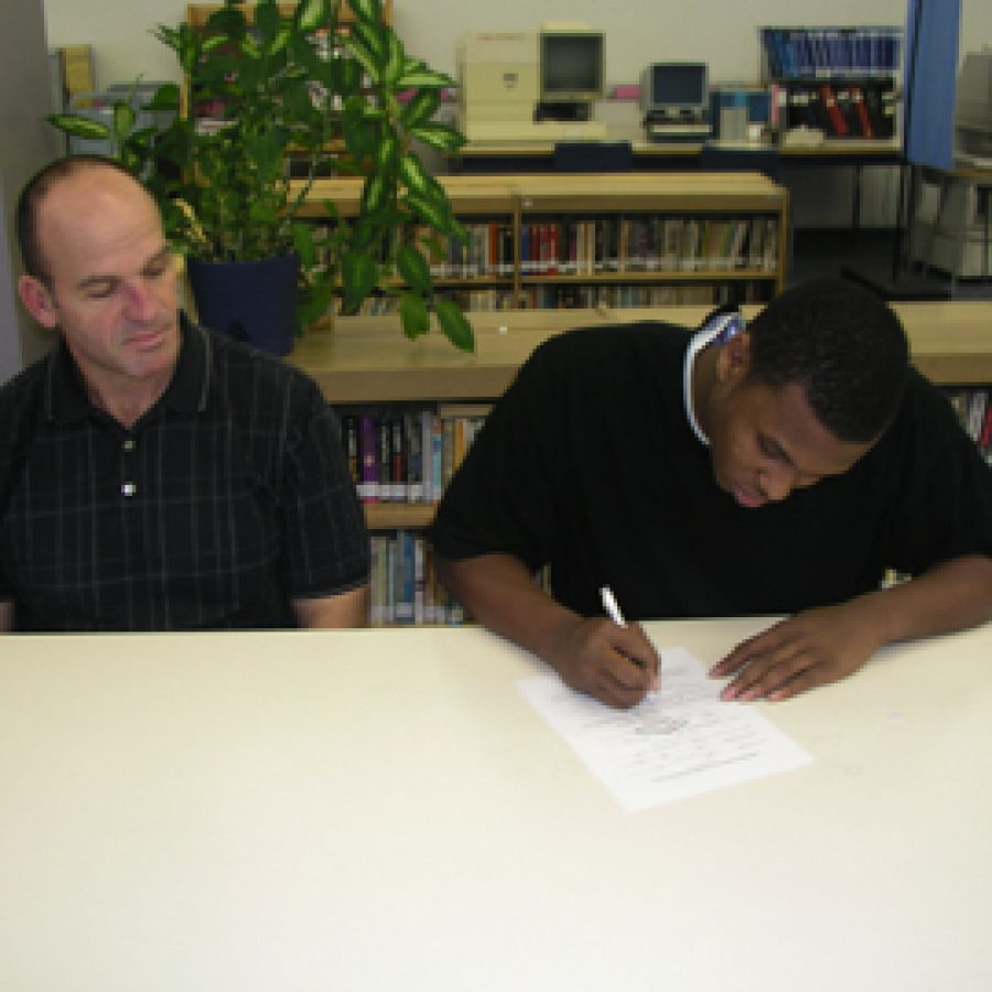 Randall Roberts, right, signs a letter of intent with Head Coach Gary Heyde looks on.