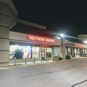 A full view of the front of Southern Armory. Standing in front of the store and looking into the shopping center from the street, the boarded-up section of the windows broken by thieves is hidden by the column at the left. Photo by Gloria Lloyd.