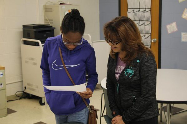 Sperreng Middle School student Daishana Finley of Amber Hardin's Digital Literacy class shows client Sam Schaeffer of Samtastic Gymnastics her design idea for a new business card.