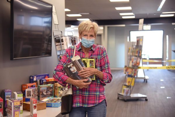 A patron picks up some books at the reopening of the St. Louis County Library