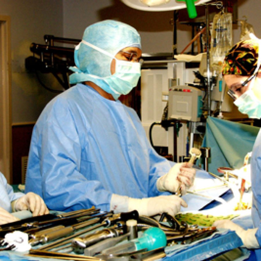 Orthopedic surgeon Dr. Ravi Shitut, center, performs the first full spinal disc replacement at St. Anthony's.  Assisting Dr. Shitut are Deborah Wagner, right, Dr. Shitut's physician assistant, and Vickie Valentine, surgical technologist.