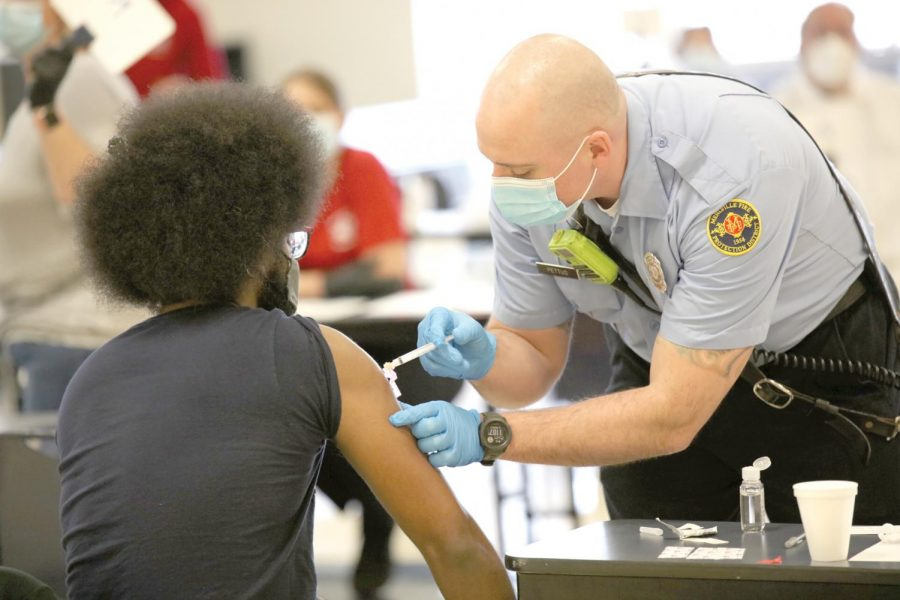 Mehlville Fire Protection District employee Kelly Pettit administers a Johnson & Johnson vaccine dose at a state-run vaccination event at Bernard Middle School Saturday, April 3.