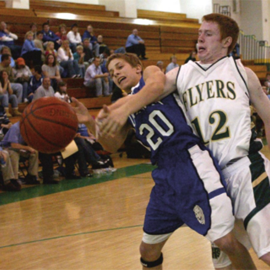 Flyer guard Rusty Stauder is called for reaching in on Northwest guard Doug Harris Friday night in a lopsided conference victory.