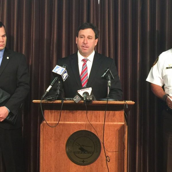 County Executive Steve Stenger announces higher police salaries June 22 along with St. Louis County Fraternal Order of Police President Joe Patterson, left, and police Chief Jon Belmar.
