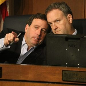 Former County Executive Steve Stenger, left, talks to then council Chairman Sam Page, D-Creve Coeur, at the Aug. 1 council meeting. Page became county executive April 19, after Stenger resigned from the position and pled guilty to federal corruption charges. Photo by Jessica Belle Kramer.