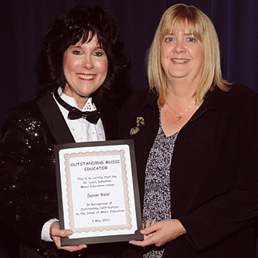 Lindbergh High School music instructor Sue Rola, left, receives the Outstanding Music Educator Award from St. Louis Suburban Music Educators board member Ann Geiler on May 3 during the LHS Spring Orchestra Concert.