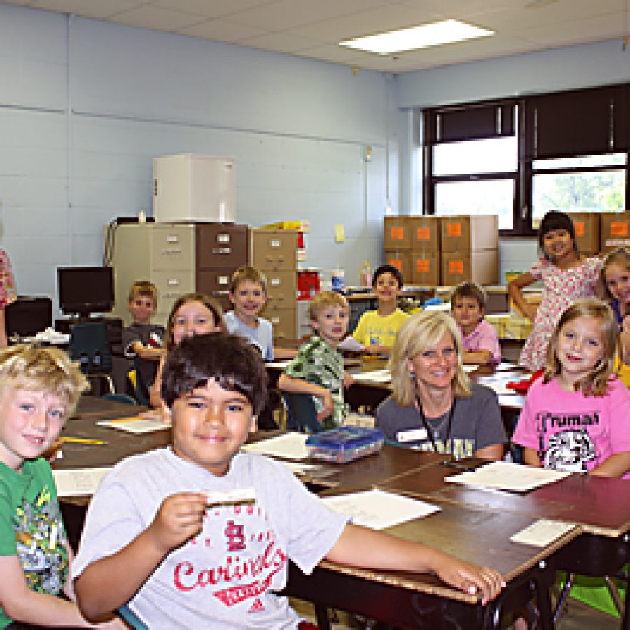First-grade students in Nancy Boughman's class take a break from last day of school activities to smile for the camera. Their teacher's moving boxes fill the room as Truman Elementary staff prepare to move out of the building this summer.