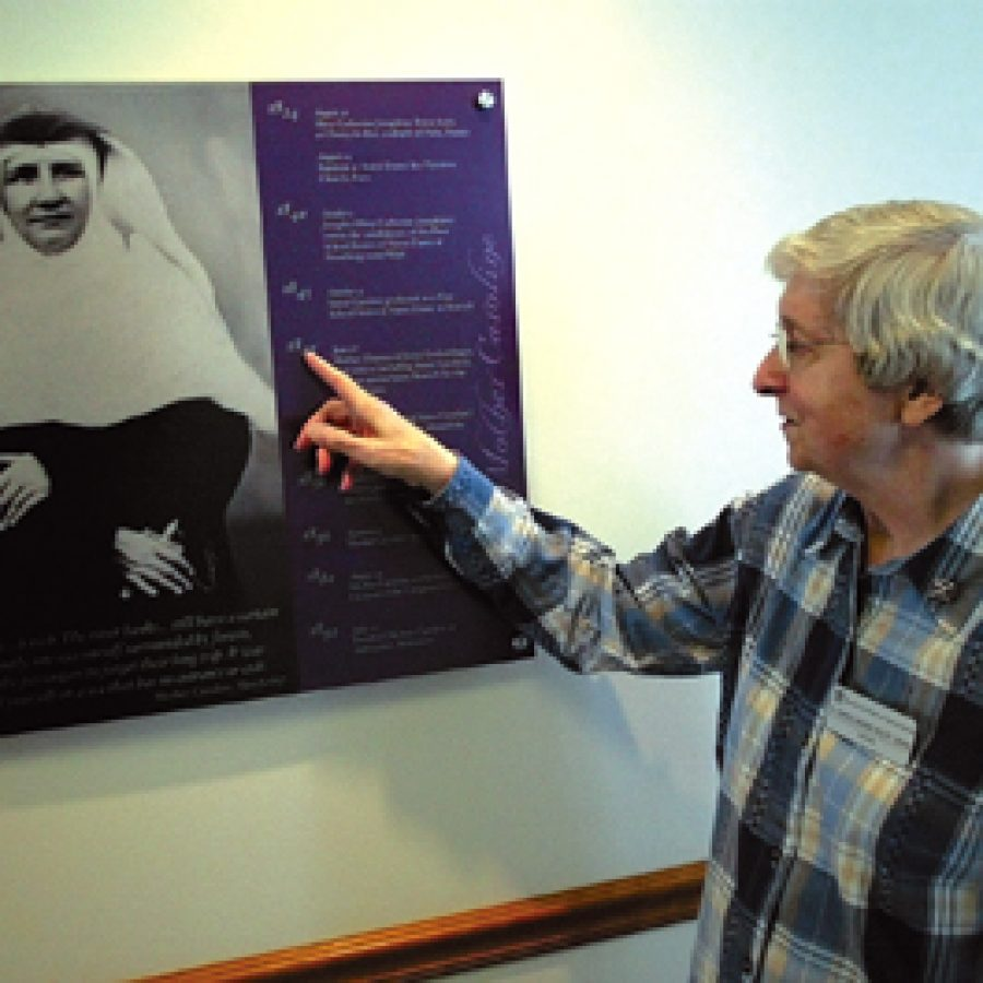 Sister Carol Marie Wildt points to a plaque outlining the accomplishments of Mother Caroline Friess. The plaque is at the visitors' entrance to the School Sisters of Notre Dame Motherhouse in Lemay.