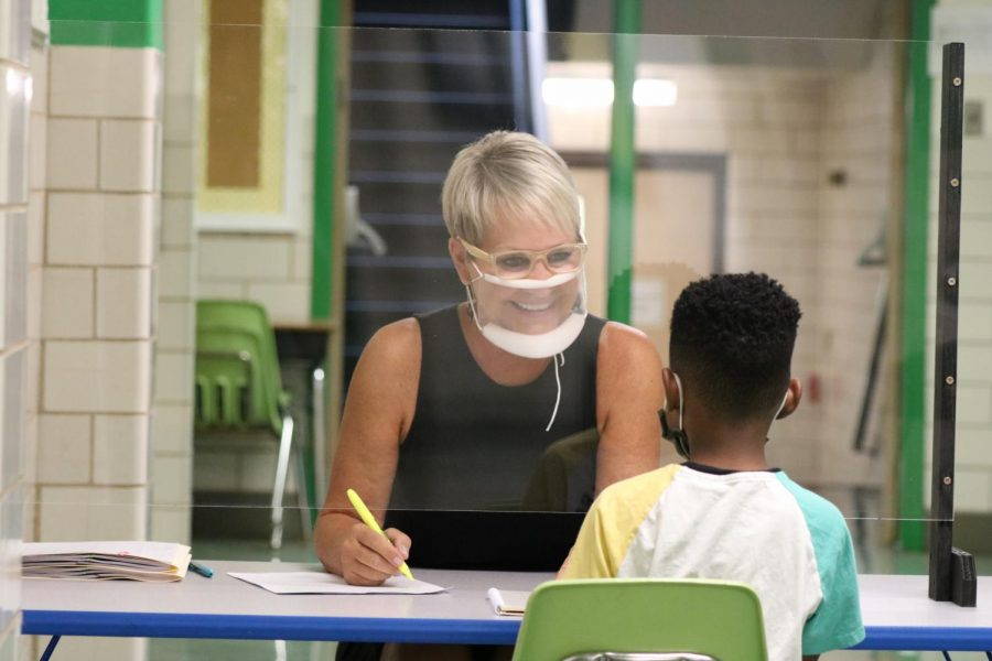 Mehlville School District's Wohlwend Elementary reading interventionist Ellen Geders meets in person with a student through a Plexiglas barrier, with masks. All students in K-12 schools have to wear masks under a new county order.