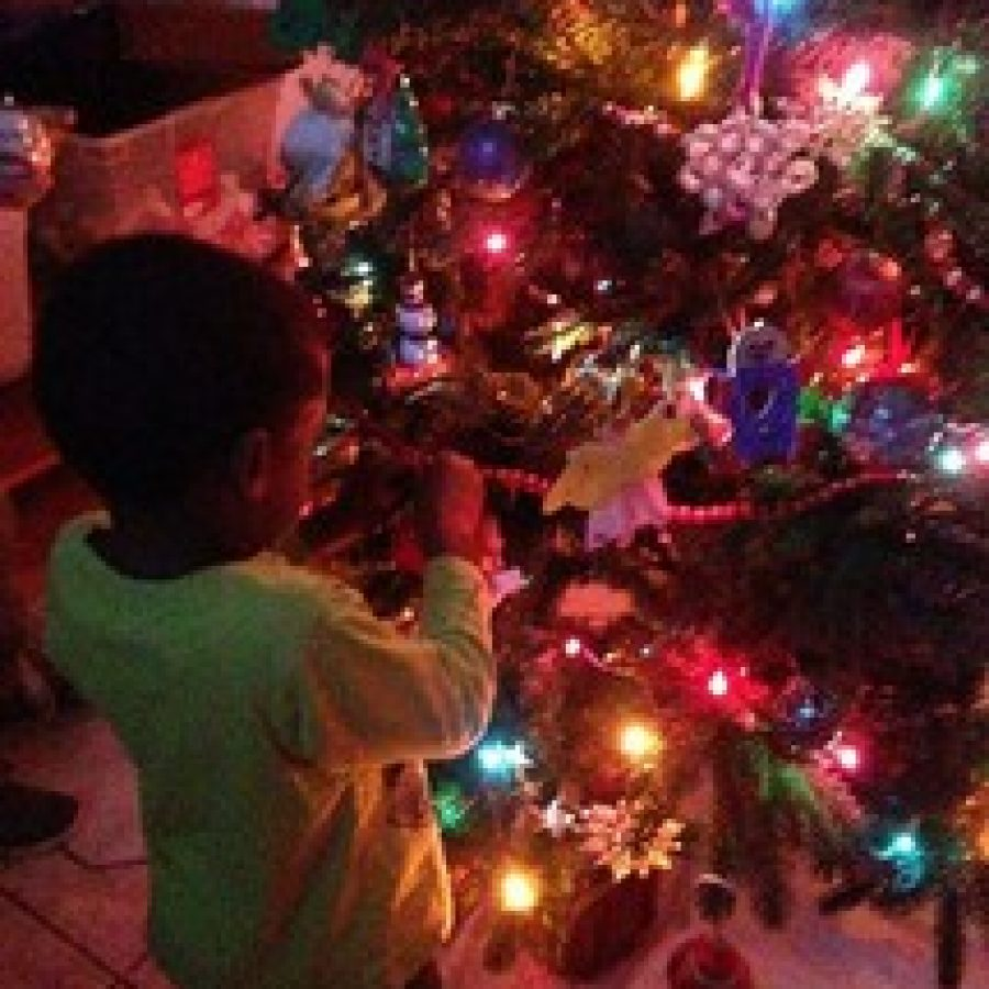 A foster child at Angels' Arms with his family's newly-decorated Christmas tree. (