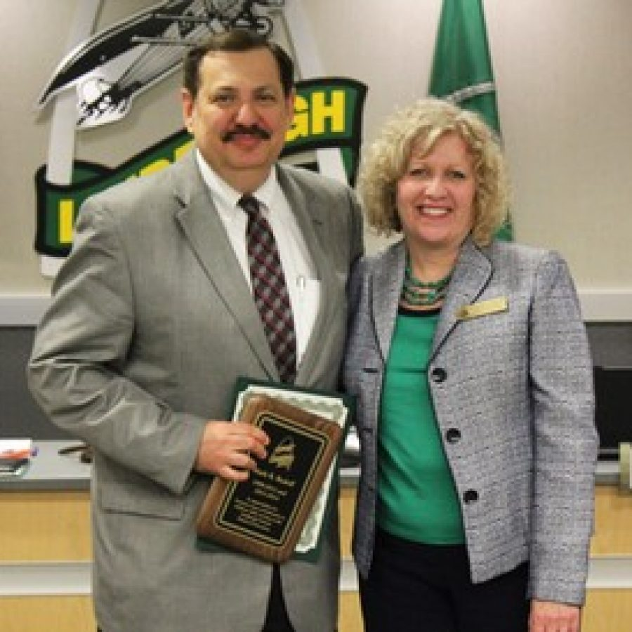 Departing Lindbergh Schools Board of Education member Mark Rudoff is presented with a resolution in honor of his service by board President Kathleen Kienstra.
