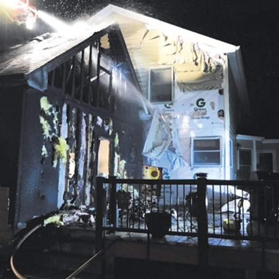 Mehlville Fire Protection District firefighters, assisted by members of the Lemay Fire Protection District, douse this deck fire at an Oakville residence.