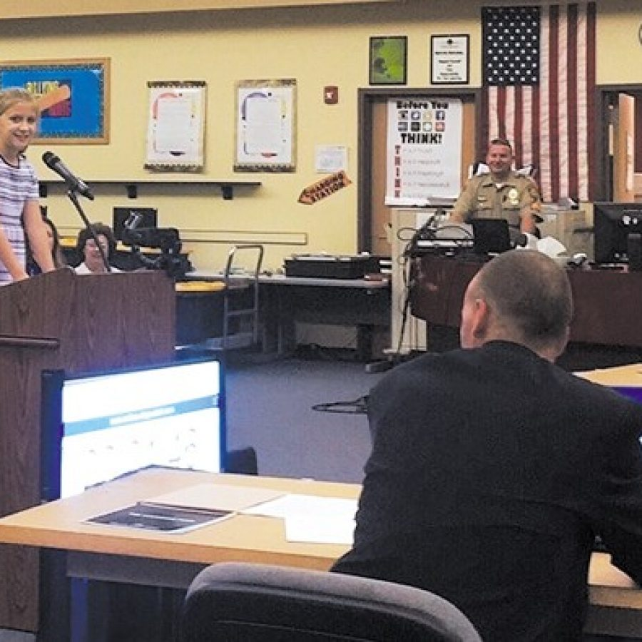 Superintendent Chris Gaines, right, listens as Rogers Elementary School third-grader Emalee Corp addresses the Mehlville Board of Education last week. 'Did you know that I plan to be president of the United States one day?' she said, asking that voters support the district's Proposition R ballot measure on Nov. 3. Pictured behind Emalee are, from left, Lemay Township Republican Committeeman Alan Leaderbrand and resident Sue Jernigan, who both spoke against Prop R at the meeting.