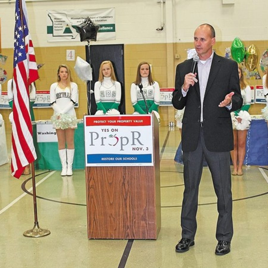 Pictured above, Superintendent Chris Gaines asks supporters at Saturday's rally for Prop R to help him get out the vote so that he can hire reading coaches and keep experienced teachers in the district. Behind him are the Mehlville HIgh School Pantherettes and the Oakville High School Golden Girls.