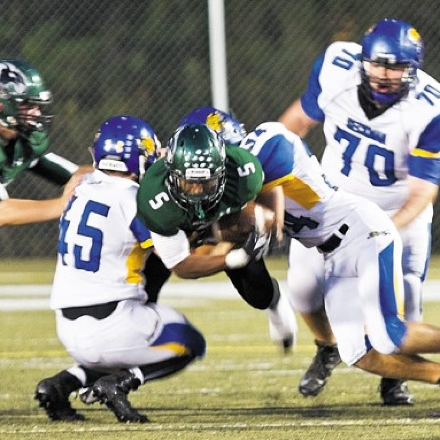 Mehlville High's Jabari Shelton, No. 5, is tackled by Seckman's Brett Winder, No. 45, and Jordan Liescheidt, No. 34, in Friday night's game. Also pictured are Mehlville's Jason Landwehr, No. 64, and Seckman's Jacob Vogel, No. 70.