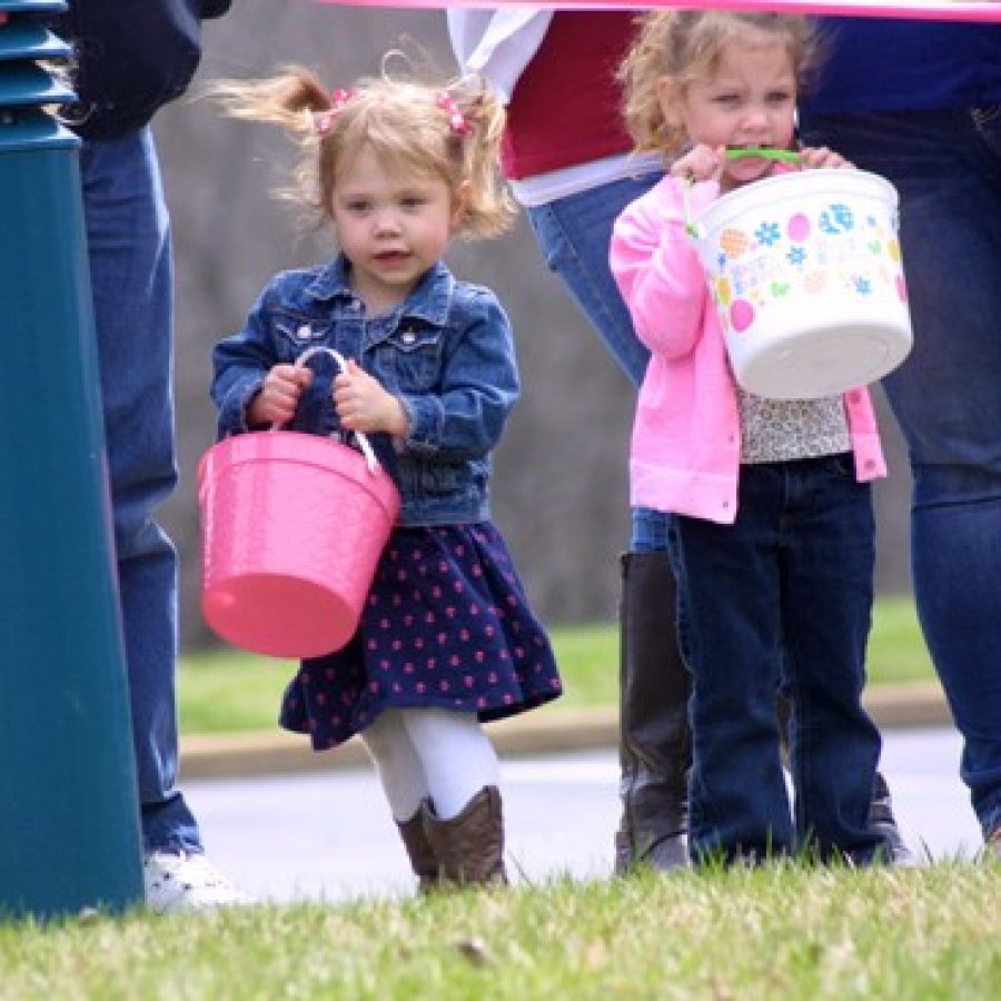 Three-year-olds Makenzie Hoffman, left, and Natalie Curtis are eager with anticipation as they can't wait to begin collecting eggs at the Easter 'Eggstravaganza' Sunday afternoon at Delmar Gardens South and Garden Villas South.