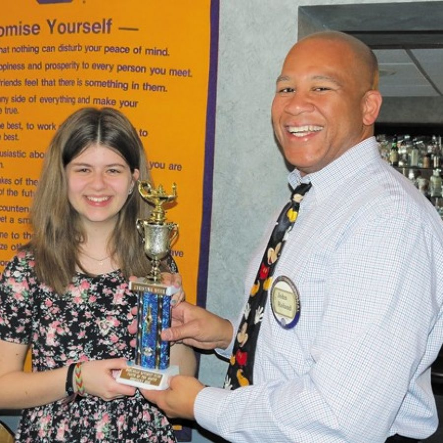 Bernard Middle School student Christina Meier, left, accepts her Student of the Month Award from John Roland, right.