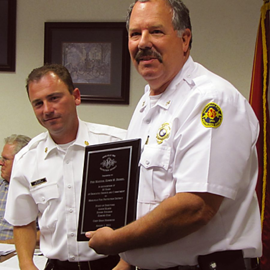 Mehlville Fire Marshal Ed Berkel, right, receives a plaque honoring his 30 years of service to the fire district from interim Chief Brian Hendricks.