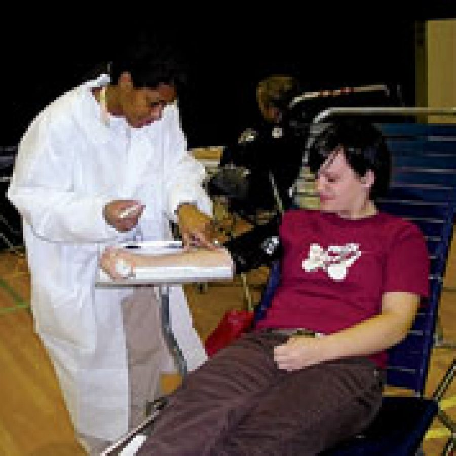 Red Cross phlebotomist Sunnie Thomas, left, assists Mehlville senior Sara Gaebler at the Student Council-sponsored blood drive.