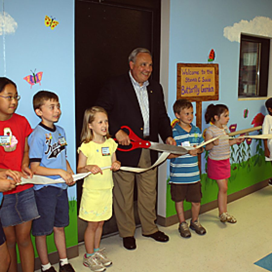 Former Kennerly Elementary School Principal Steven C. Suess cuts a ribbon celebrating a new butterfly garden that has been dedicated in his honor. The mural behind him was painted by art teacher Ann Clifton and features butterfly drawings made by pupils.
