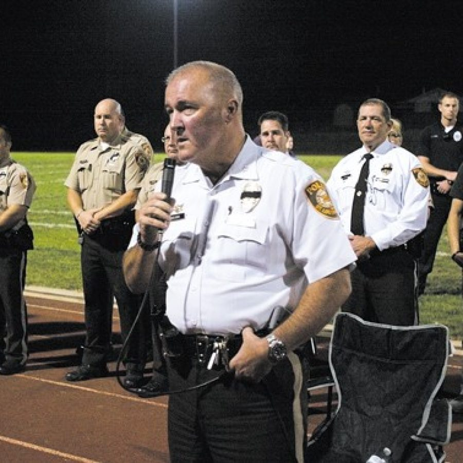 St. Louis County Police Chief Jon Belmar, foreground, thanks the roughly 1,000 people who attended a candlelight vigil Oct. 6 to honor Officer Blake Snyder, who was shot and killed earlier that day as he responded to a call in Green Park. Behind Belmar, first responders line up at the Affton High School football field to show their support for Officer Snyder.