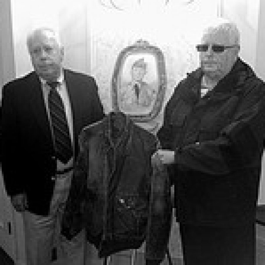 Brothers Gus and John Nelson hold a military jacket that belonged to their uncle, Cpl. James Larkin, Jr., who was killed in the Korean War in 1951. Larkin's remains were returned to the U.S. in 2006 but were not positively identified until this year. A photo of Larkin in his uniform is in the background.  Photo by Lt. Col. Kevin McGhee