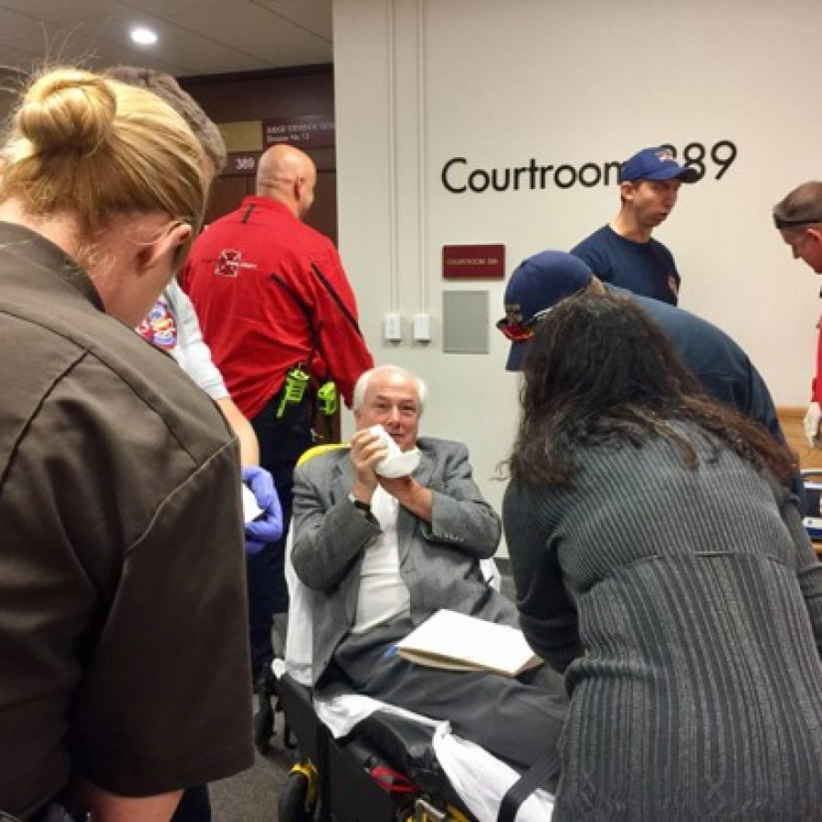 Clayton and Mehlville parademics assist reporter Tim O'Neil, sitting, after losing part of a finger Nov. 9 at the St. Louis County Courthouse.