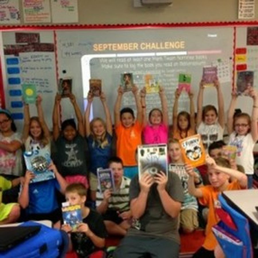 Students in Mallory Krueger's fifth-grade classroom at Sappington Elementary pose with their books, which need bookshelves, for Krueger's DonorsChoose request.