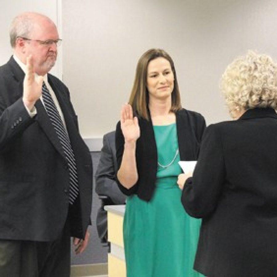 Lindbergh Board of Education President Kathy Kienstra, right, swears in new board members Mike Tsichlis and Jennifer Miller at last week's board meeting.