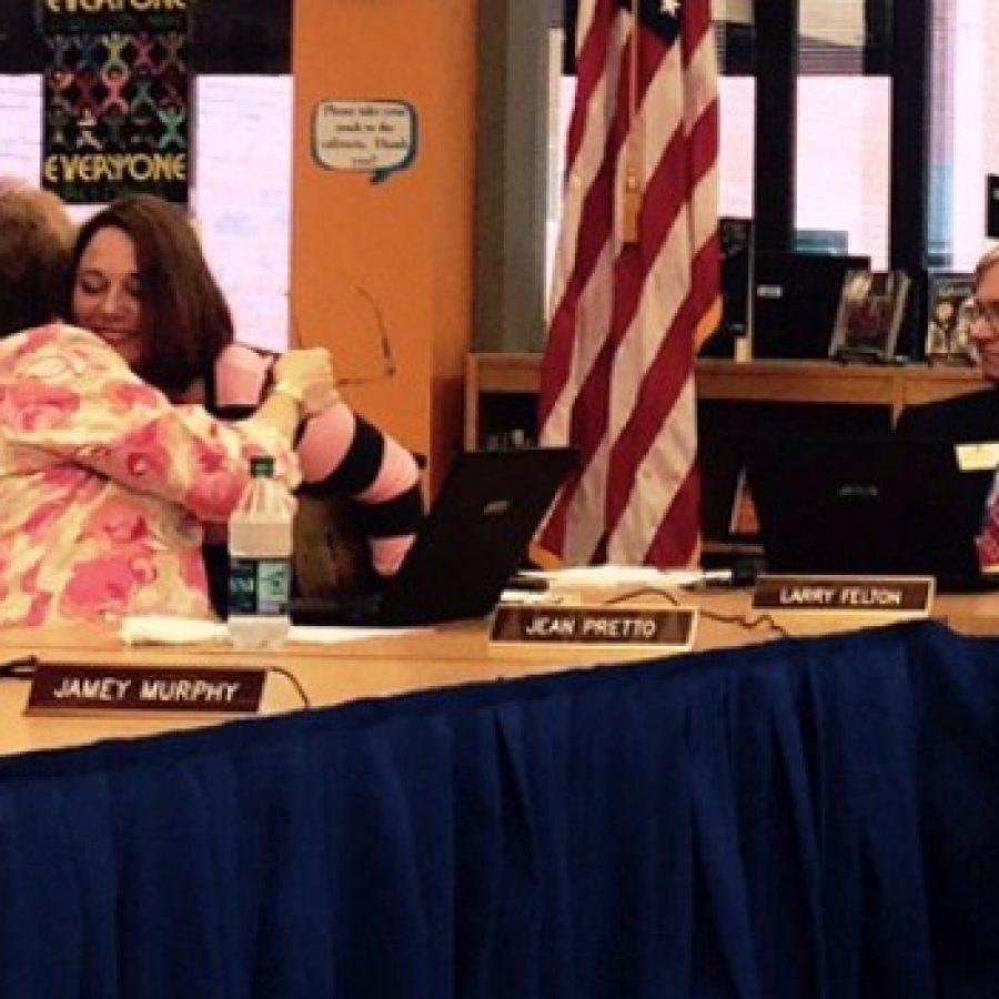 Board Vice President Jean Pretto, left, hugs exiting board member Lori Trakas as she leaves when her last meeting adjourned last week. Also pictured is board member Larry Felton.