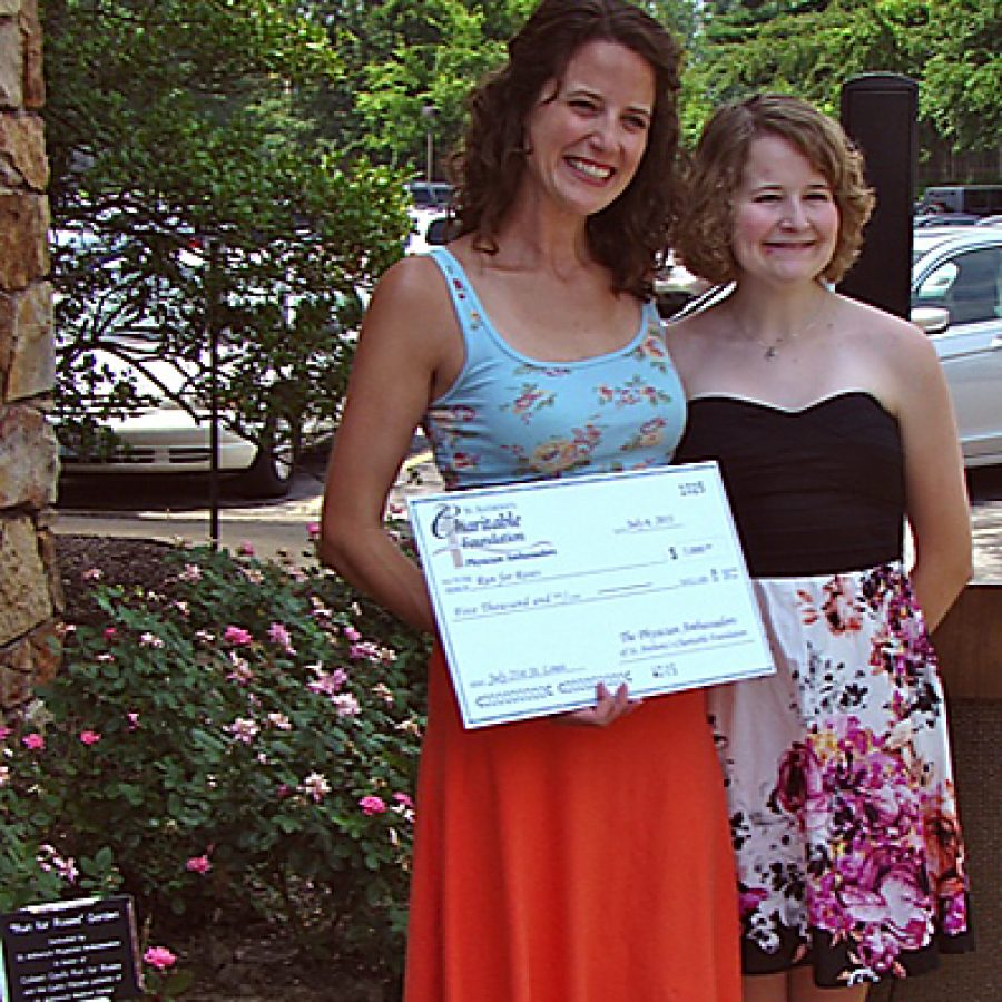 Colleen Caul, left, is pictured with her sister, Katie Rose, on July 6 in front of the \Run for Roses\ Garden at the St. Anthonys Medical Center Hyland Education and Training Center. The Physician Ambassadors of the St. Anthonys Medical Center Charitable Foundation dedicated the garden and presented a check in honor of Run for Roses, Cauls upcoming 65-day trek from St. Louis to New York City to raise funds for the Cystic Fibrosis Foundation. Katy Forand photo