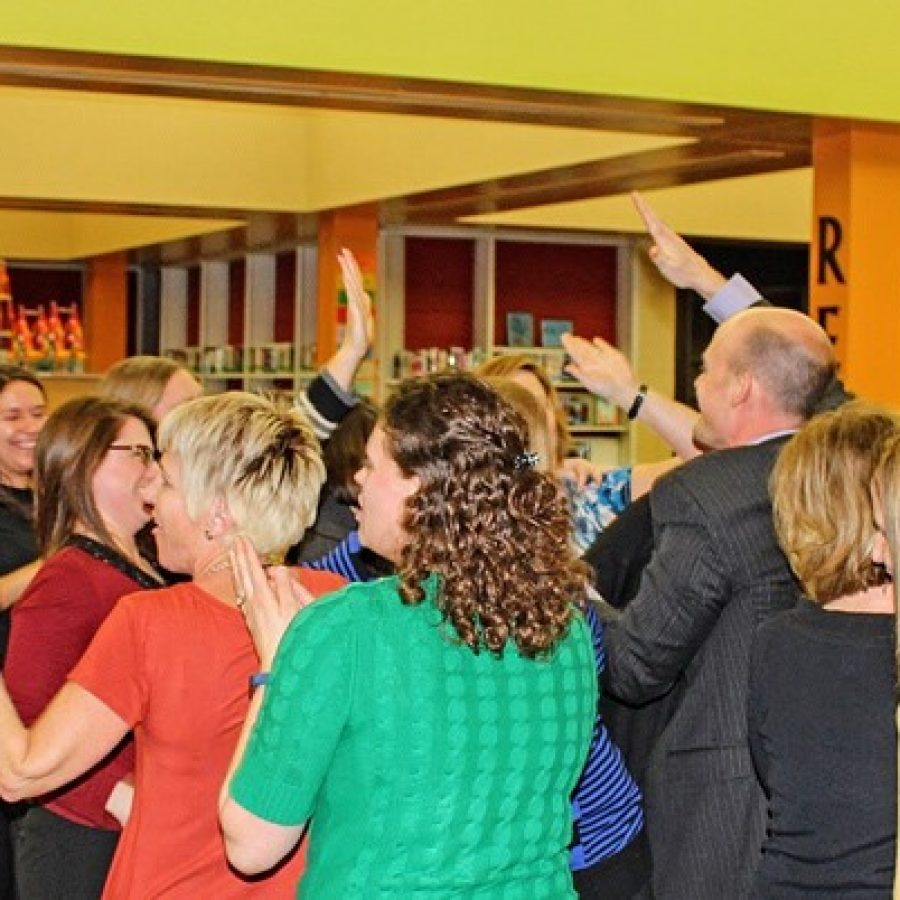 Teachers for the new Mehlville school of innovation celebrate with Forder Principal Scott Clark after the Board of Education approved it Wednesday night.