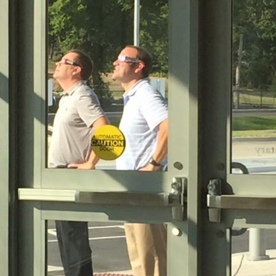 Lindbergh Schools' Dressel Elementary Principal Craig Hamby, left, and Assistant Principal Patrick Schoenekase try out some of the schools' eclipse glasses last week to see if they will stand up to the sun's rays.