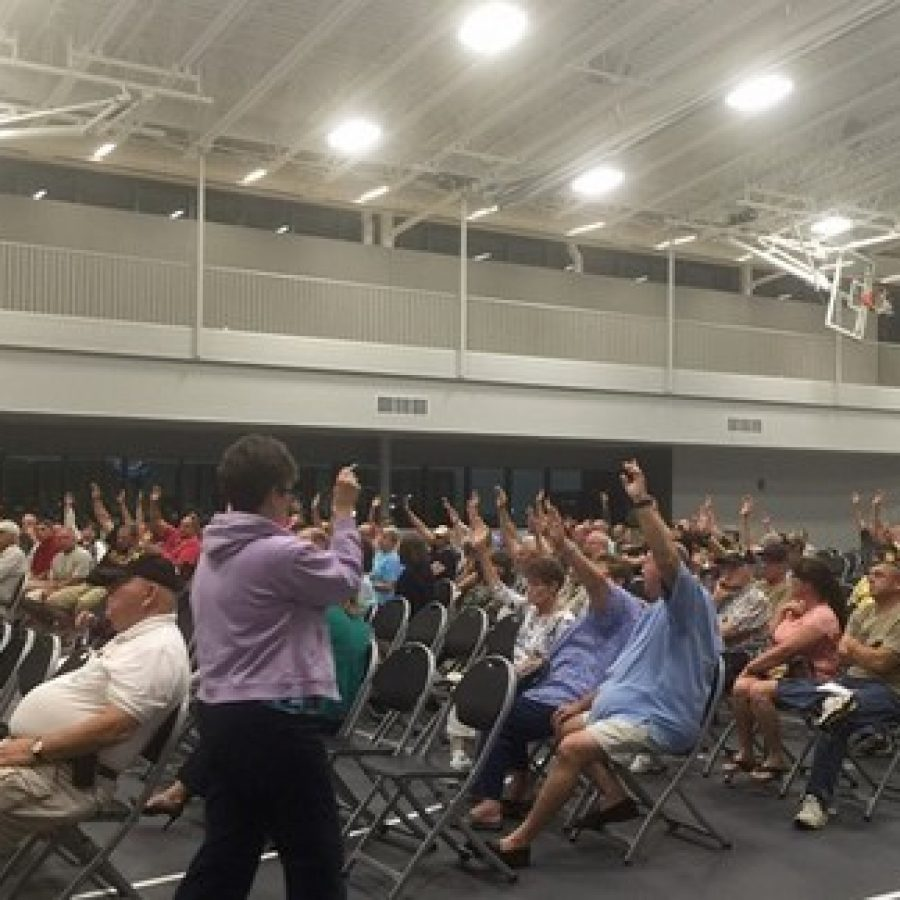 The crowd at one of the Sylvan Springs public hearings raises its hands in favor of selling the park to the Jefferson Barracks National Cemetery, as counted by county land-use manager Gail Choate. Photo by Gloria Lloyd.