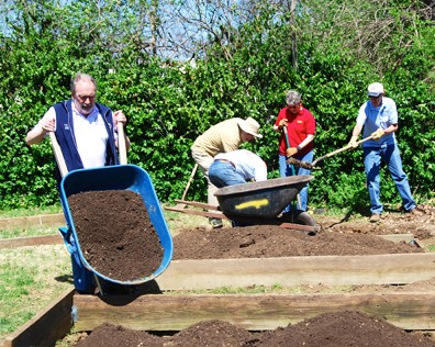 Former Kiwanis International President Dr. John Button helps local Kiwanians beautify gardens and the lawn at Angels' Arms' South County house during his visit.