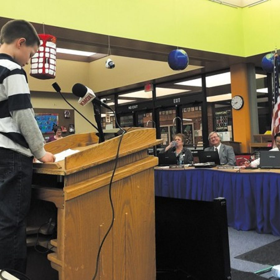 Point Elementary second-grader Dylan Lohrke, 7, speaks to the Mehlville Board of Education last month to ask them not to cut teachers, buses, custodians or the gifted program STRETCH. Also pictured are board members, from left, Jean Pretto, Larry Felton and Venki Palamand.