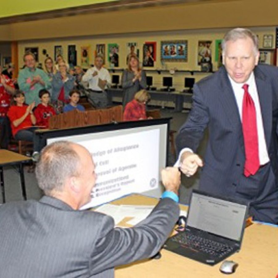 Dan Fowler, right, fist bumps Superintendent Chris Gaines after the naming vote.