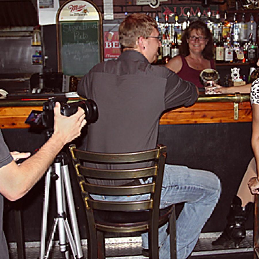 At the Stone House East Pine Pub in Warrensburg, director and writer David Skaggs, of Oakville, a University of Central Missouri student, left, sets up a shot for a 10-minute supernatural film that he plans to enter in the second annual Show-Me Justice International Film Festival. Talent for the production, from left, are: Tim Lowndes, pub co-owner Debbie Rosebush and Nicole Santorella.