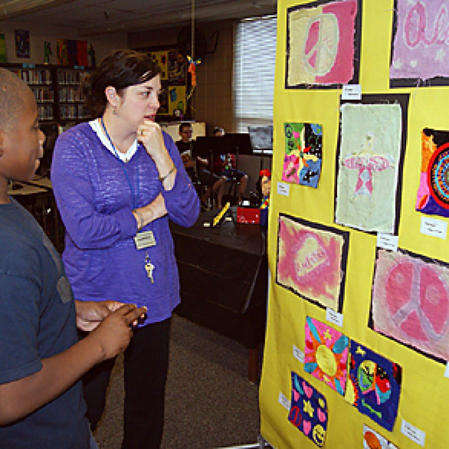 Washington Middle School sixth grader Jordan Chavers and his teacher, Mary Ellen Roungon, view the student artwork on display at the school's Fine Arts Show on May 20.