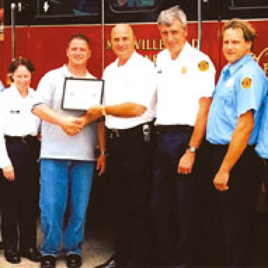 Mehlville Fire Protection District resident Kevin Driskell is honored by the fire district for his selfless and heroic efforts to evacuate residents during a fire at his condominium complex. Pictured, from left, are: Pvt. Mitch Fassler, Lt. Joanne Evans, Driskell, Deputy Chief Steve Mossotti, Capt. Nick Fahs, Pvt. Craig Dexter and Pvt. Doug Weck.