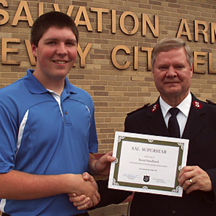 Scott Sandbach accepts his award for outstanding achievement from Capt. Kirk Schuetz of the Gateway Citadel Salvation Army.