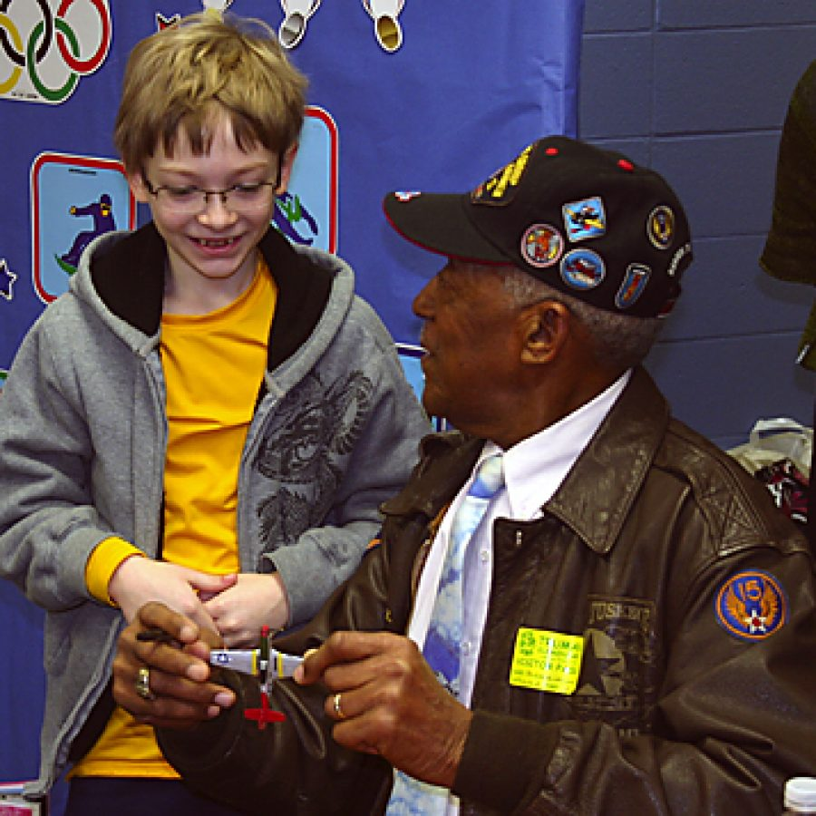 George Watson Sr. autographs a model airplane for Truman Elementary fifth-grader Alex Nejelski.
