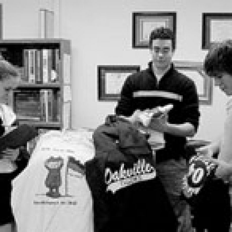 Oakville students, from left, Nikki Hobbs, Jordan Mroz and Nate Hoffman, take inventory of a recent shipment for 'Tiger T's' and prepare the German Club order for delivery.