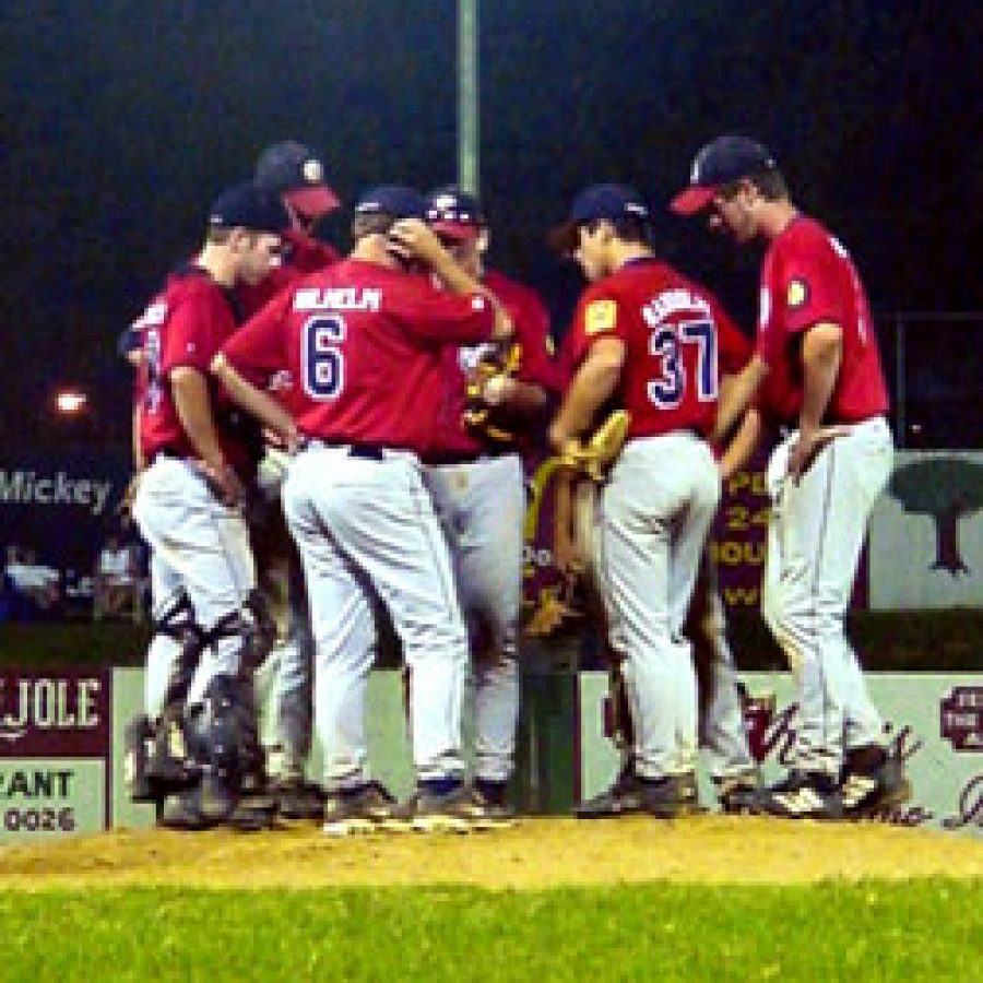 Head coach Mike Wilhelm calls his troops to the mound during the eighth inning of Oakville's 7-6 win over Lemay Sunday evening.