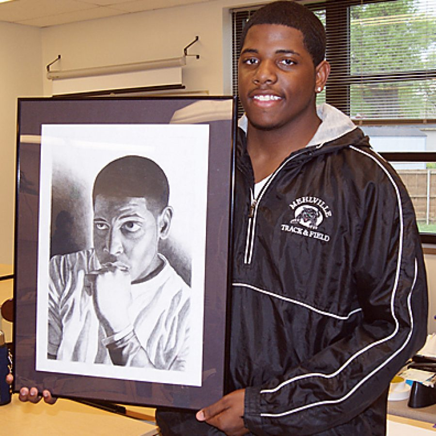 MHS senior Juan Edwards poses with his charcoal self-portrait titled \
