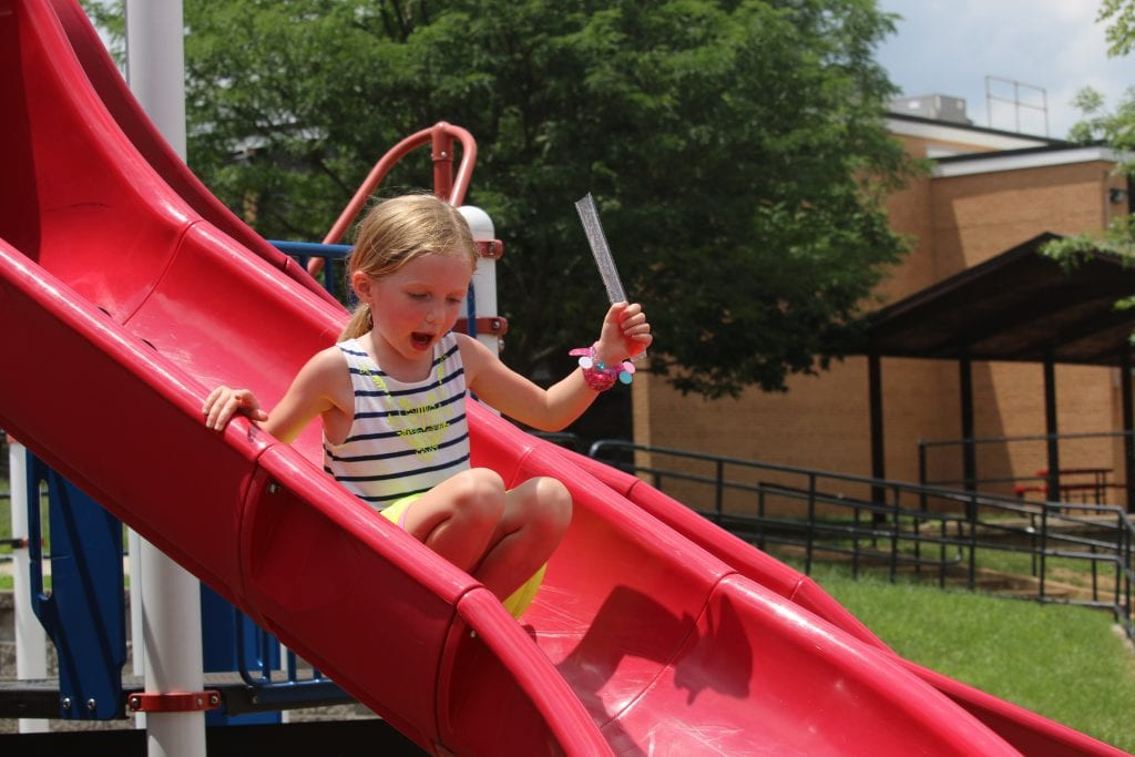 An+incoming+Kennerly+kindergartener+slides+at+%27Popsicles+with+the+Principal%27+in+2018+on+the+school%27s+playground.++Photo+by+Jessica+Belle+Kramer.