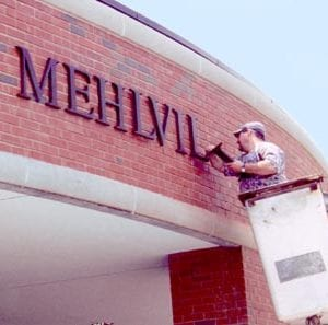 A worker places new letters on the front of Mehlville Senior High School as one of the final touches of Proposition P improvements at the school. Prop P was approved by voters in 2000, and was one of the last times Mehlville made a significant investment in its facilties.